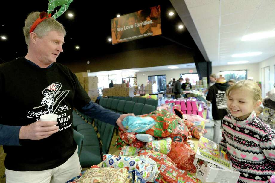 Retired New York police officer Kevin Leonard offers Kaleigh Smith a surprise stuffed animal toy as he helps during the toy distribution held by members of the New York Fire Department and other volunteers at Community Christian Church in Orange Saturday. Retired and active members of the NYFD held the event at three area churches, including North Baptist Church in Orange and St. Anthony's Basilica in Beaumont. It was part of the Stephen Siller Foundation Tunnel to Towers' efforts to help bring Christmas to families throughout Southeast Texas in the wake of Tropical Storm Harvey's devastating impact on the community. Photo taken Saturday, December 9, 2017 Kim Brent/The Enterprise Photo: Kim Brent / BEN