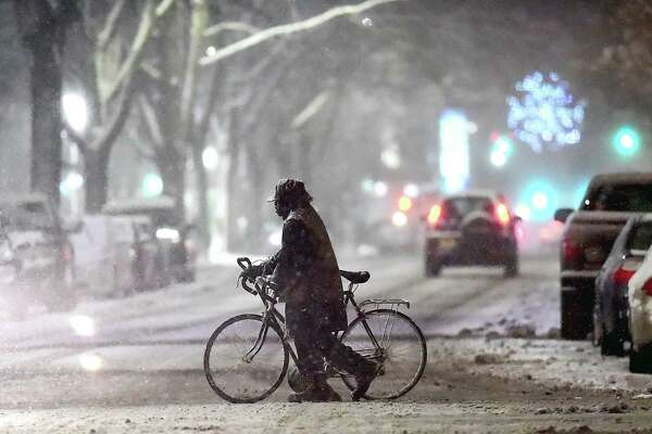 A cyclist walks his bike across College Street in New Haven carrying a shovel during the first snow fall of the season,  Saturday, Dec. 9, 2017. According to the National Weather Service, a storm system will spread heavy snow from portions of the Middle Atlantic to the Northeast and New England into Sunday.  #ctweather