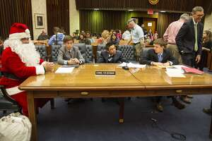 Santa Claus, also known as Luis Miranda, sits with his defense attorneys — Patrick Hughes, 14 (from left); Logan Balfour, 13; and Quinn Niebergall, 13, Boy Scouts from Troop 285 — Saturday in U.S. District Judge Henry J. Bemporad's courtroom at the federal courthouse. This is the 24th year of the mock trial, which is a community service project organized by the U.S. District Court Committee, San Antonio Bar Association, Boy Scouts Troop 285 and James Bonham Academy.