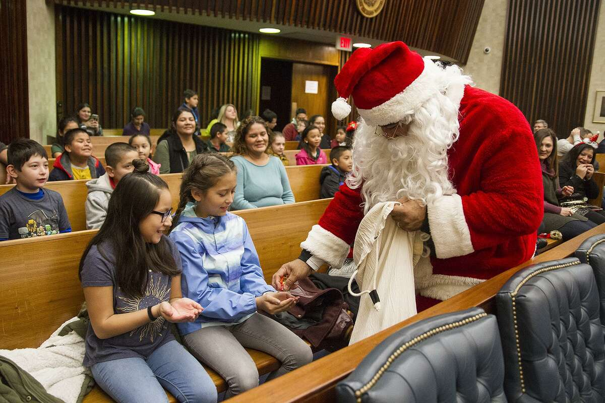 Luis Miranda as Santa hands out candy to Skylar Robertson (center), 9, and Calina Gonzales, 9, while he waits for a verdict Saturday. Santa was found not guilty of endangering children and violating the law that separates church and state.
