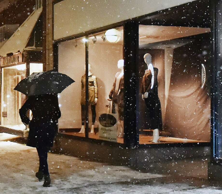 A mannequin in a window appears to be watching a woman walking with an umbrella on Chapel Street in New Haven during the snow storm, Saturday, Dec. 9, 2017.  #ctweather Photo: Catherine Avalone, Hearst Connecticut Media / New Haven Register