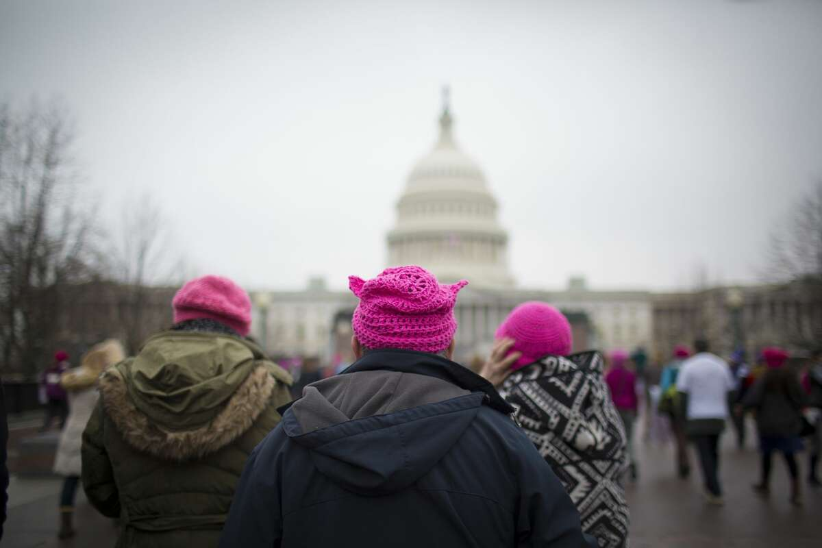 Three pink-topped members of a crowd estimated at 400,000 to 500,000 make their way toward the U.S. Capitol as part of the Women's March the day after Donald Trump's inauguration. The knit hats were worn by many who showed up in opposition to Trump.