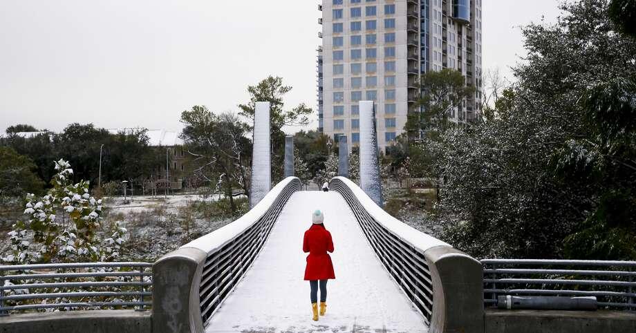 Olivia Park strolls through the snow across the Jackson Hill Bridge in Buffalo Bayou Park. Photo: Michael Ciaglo/Houston Chronicle
