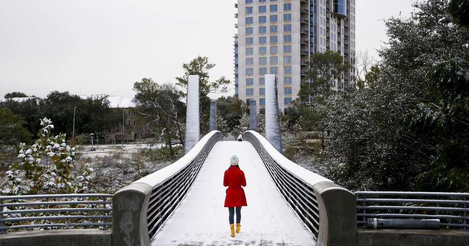 After an overnight storm blew snow into Houston, residents rushed outside in the morning to enjoy the surprise before it melted. Olivia Park strolls through the snow across the Jackson Hill Bridge in Buffalo Bayou Park. Photo: Michael Ciaglo/Houston Chronicle