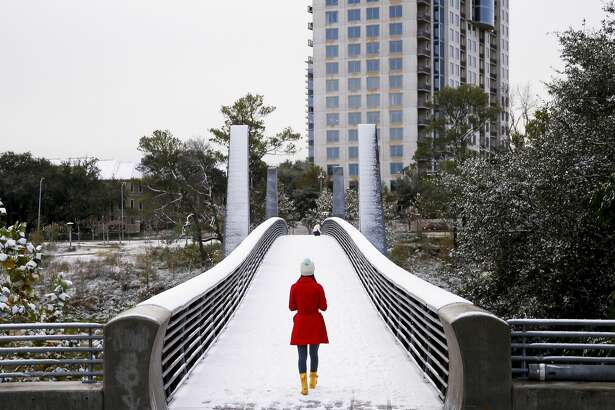 After an overnight storm blew snow into Houston, residents rushed outside in the morning to enjoy the surprise before it melted. Olivia Park strolls through the snow across the Jackson Hill Bridge in Buffalo Bayou Park.