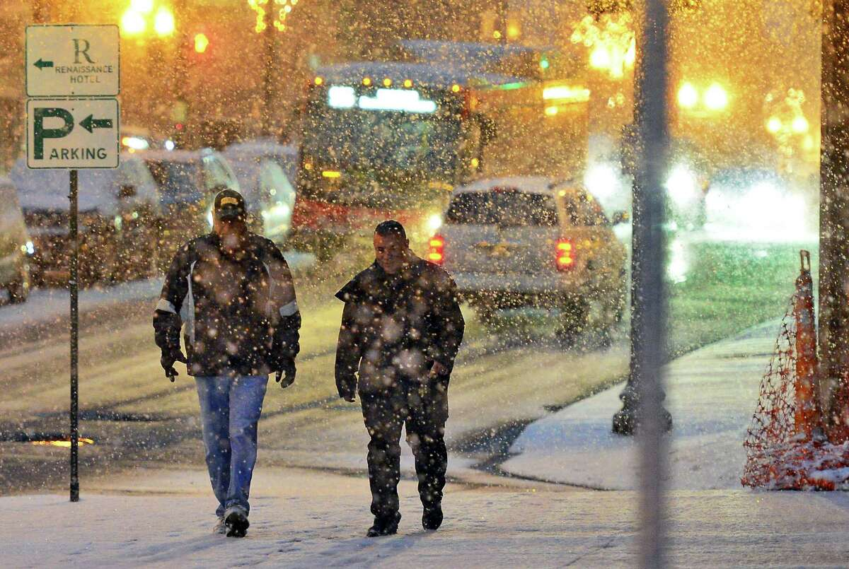 Two men make their way along South Pearl Street as the season's first snows hit the Capital Region Saturday Dec. 9, 2017 in Albany, NY. (John Carl D'Annibale / Times Union)