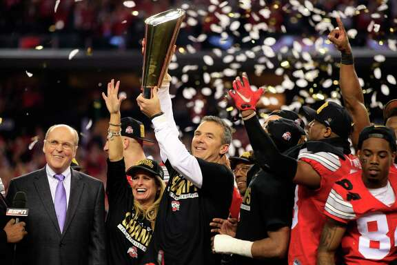 ARLINGTON, TX - JANUARY 12:  Head Coach Urban Meyer of the Ohio State Buckeyes hoist the trophy after defeating the Oregon Ducks 42 to 20 in the College Football Playoff National Championship Game at AT&T Stadium on January 12, 2015 in Arlington, Texas.  (Photo by Jamie Squire/Getty Images) ***BESTPIX***