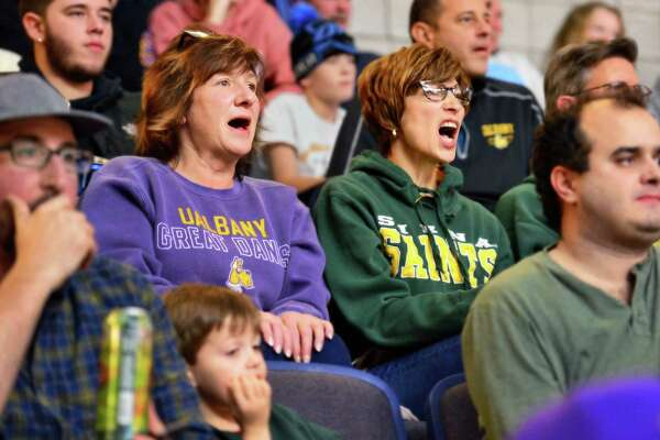 Sisters Michelle Wolsey, left, of Ballston Spa and Maria Guyette of Albany root for opposing teams during the Albany Cup game between UAlbany and Siena College Saturday Dec. 9, 2017 in Albany, NY.  (John Carl D'Annibale / Times Union)