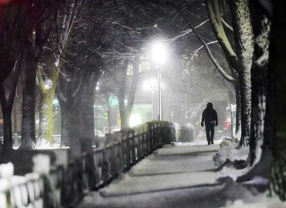 A gentleman walks down College Street in New Haven, Saturday, Dec. 9, 2017, during the first snow fall of the season. According to the National Weather Service, a storm system will spread heavy snow from portions of the Middle Atlantic to the Northeast and New England into Sunday.  #ctweather Photo: Catherine Avalone / Hearst Connecticut Media / New Haven Register