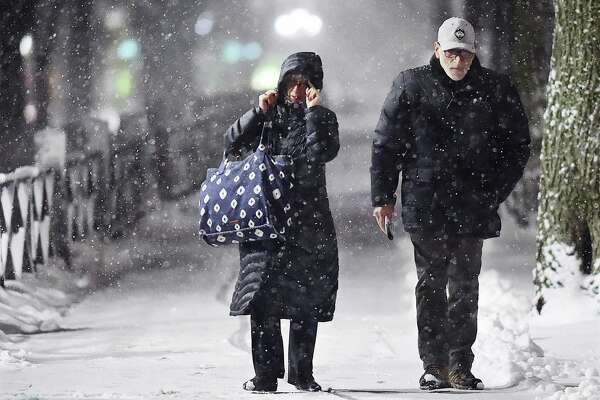 A couple braves the first snowfall of the season walking on College Street along the New Haven Green, Saturday, Dec. 9, 2017. According to the National Weather Service, a storm system will spread heavy snow from portions of the Middle Atlantic to the Northeast and New England into Sunday. #ctweather