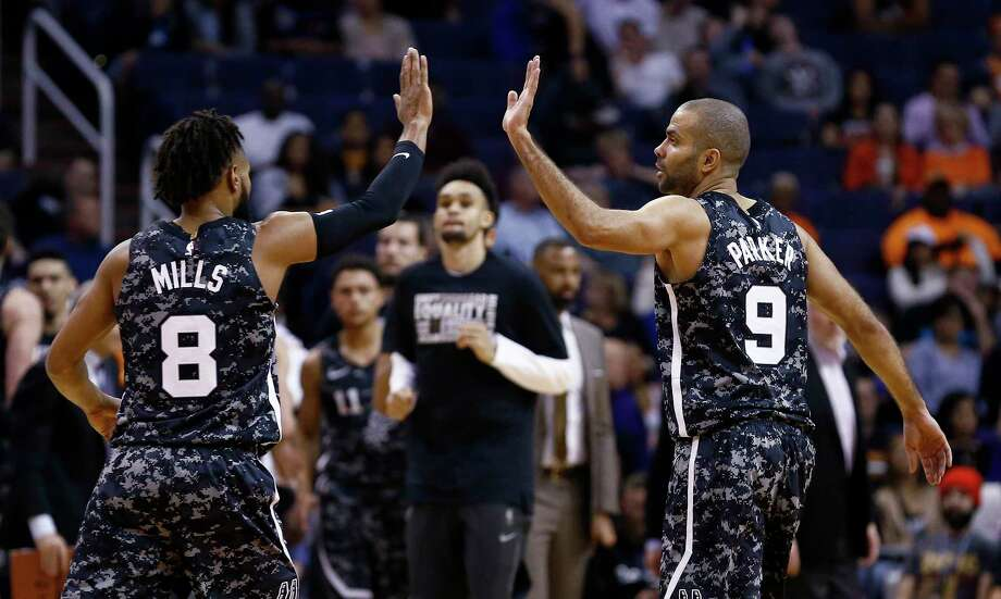 San Antonio Spurs guards Tony Parker (9) and Patty Mills (8) high-five after a scoring run forcd the Phoenix Suns to take a timeout during the first half of an NBA basketball game Wednesday, Feb. 7, 2018, in Phoenix. (AP Photo/Ross D. Franklin) Photo: Ross D. Franklin, Associated Press / Copyright 2018 The Associated Press. All rights reserved.