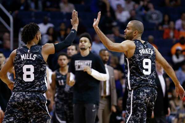 San Antonio Spurs guards Tony Parker (9) and Patty Mills (8) high-five after a scoring run forcd the Phoenix Suns to take a timeout during the first half of an NBA basketball game Wednesday, Feb. 7, 2018, in Phoenix. (AP Photo/Ross D. Franklin)