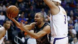 San Antonio Spurs forward Davis Bertans (42) passes the ball around Phoenix Suns center Greg Monroe during the first half of an NBA basketball game Saturday, Dec. 9, 2017, in Phoenix. (AP Photo/Ralph Freso)