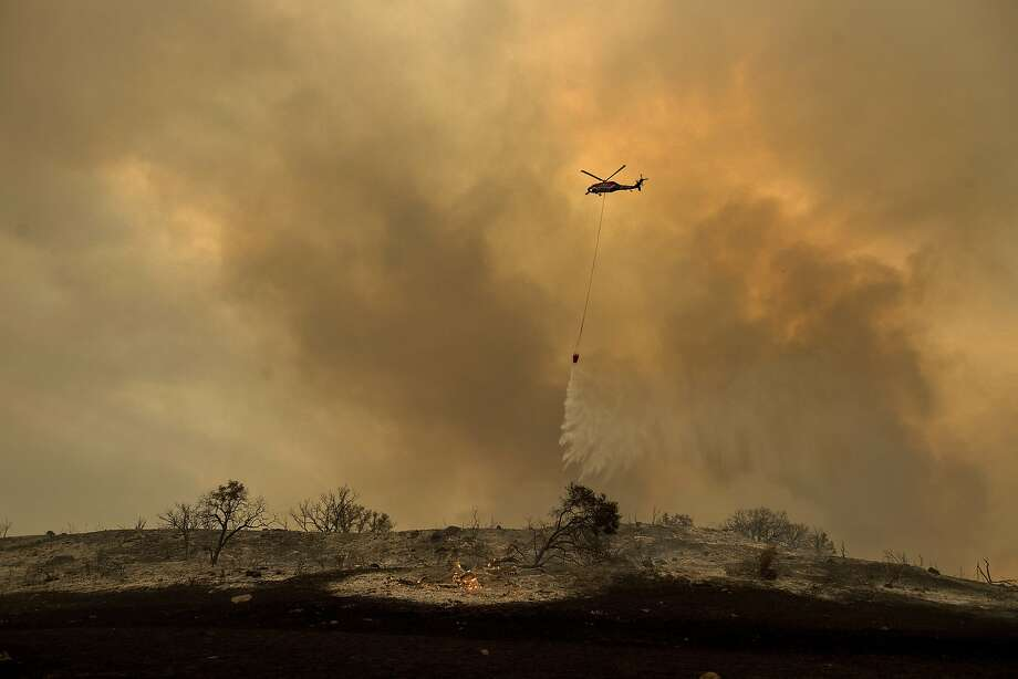 A helicopter drops water while trying to keep a wildfire from jumping Santa Ana Road near Ventura on Saturday. Photo: Noah Berger, Associated Press