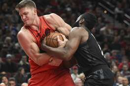 Portland Trail Blazers center Meyers Leonard and Houston Rockets guard James Harden tie each other up, resulting in a jump ball call during the first half of an NBA basketball game in Portland, Ore., Saturday, Dec. 9, 2017. (AP Photo/Steve Dykes)
