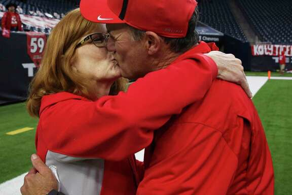 Sheila Joseph gives her husband a celebratory kiss after Gary Joseph coached Katy into the Class 6A Division I state semifinals with a 31-3 victory over North Shore on Saturday, running the Tigers' record to 11-0 this season.