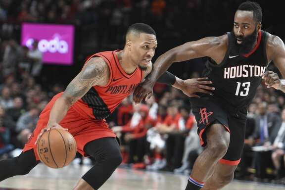 Portland Trail Blazers guard Damian Lillard drives to the basket on Houston Rockets guard James Harden during the second half of an NBA basketball game in Portland, Ore., Saturday, Dec. 9, 2017. The Rockets won 124-117. (AP Photo/Steve Dykes)