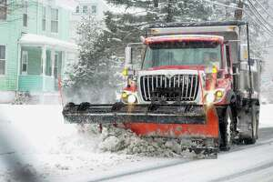 A snow plow makes its way along Howe Ave in Shelton, Conn., on Saturday Dec. 9, 2017.