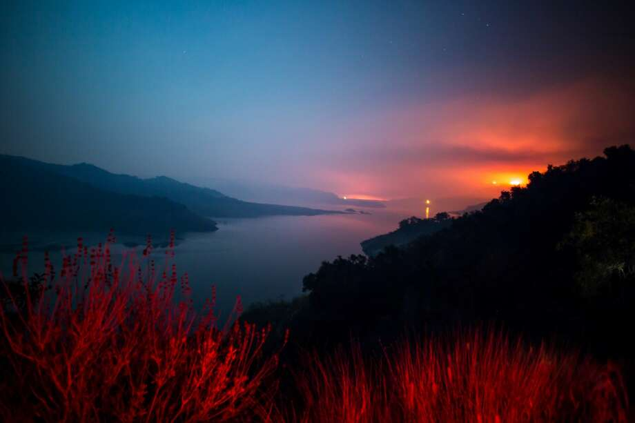 The Thomas Fire burns a hillside behind Lake Casitas in Ventura, California on December 8, 2017.  Firefighters are continuing to battle raging wildfires across southern California that have forced tens of thousands of people to flee their homes, including residents on the outskirts of Los Angeles, America's second-largest city. / AFP PHOTO / Kyle Grillot Photo: KYLE GRILLOT/AFP/Getty Images