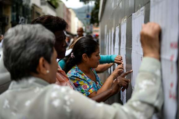 People look for their names on electoral rolls before voting in the municipal elections in Caracas on December 10, 2017. / AFP PHOTO / FEDERICO PARRAFEDERICO PARRA/AFP/Getty Images
