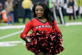 Honorary Houston Texans Cheerleader Simone Biles stands on the field before an NFL football game between the Houston Texans and the San Francisco 49ers, Sunday, Dec. 10, 2017, in Houston. (AP Photo/David J. Phillip)