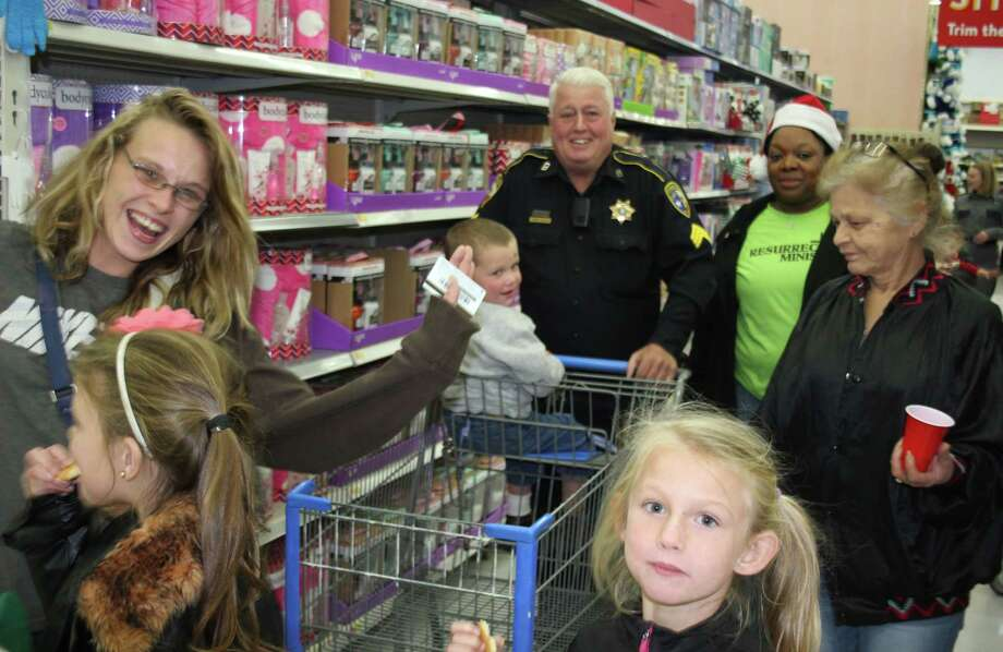 Larry Adams (back) of the Liberty County Pct. 6 Constable's Office shops with a family on Dec. 8 at the Shop with a Cop event held at Cleveland Walmart. Photo: Jacob McAdams