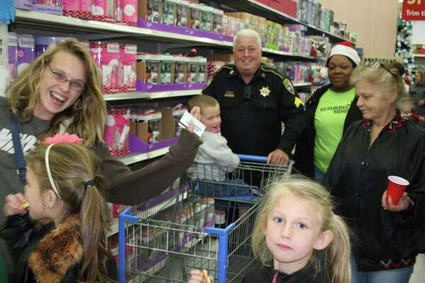 Larry Adams (back) of the Liberty County Pct. 6 Constable's Office shops with a family on Dec. 8 at the Shop with a Cop event held at Cleveland Walmart.