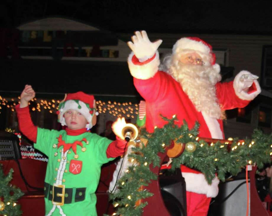 Santa Claus and an elf wave to the crowd in Coldspring at the Christmas on the Square parade held on Dec. 9. Photo: Jacob McAdams