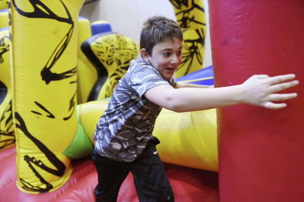 Riverside's Teddy Auerbach, 9, runs on the inflatable obstacle course at the Chanukah Celebration at Temple Sholom in Greenwich, Conn. Sunday, Dec. 10, 2017. The party featured traditional latkes and donuts, an inflatable obstacle course for kids, edible dreidels and menorahs, face painting and other games for kids.