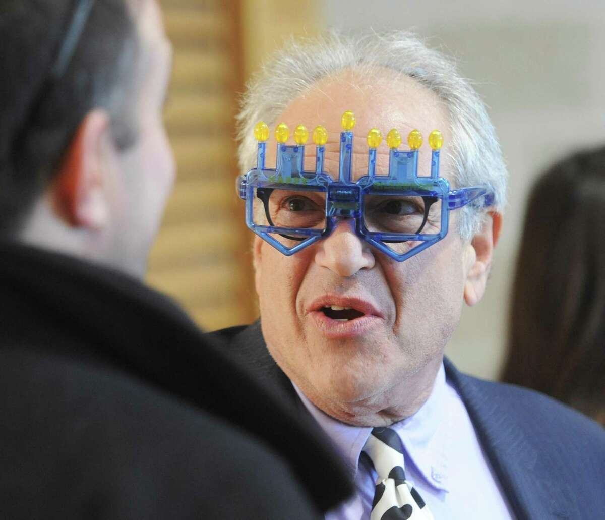 Temple Sholom Director of Education Barry Gruber wears menorah glasses at the Chanukah Celebration at Temple Sholom in Greenwich, Conn. Sunday, Dec. 10, 2017. The party featured traditional latkes and donuts, an inflatable obstacle course for kids, edible dreidels and menorahs, face painting and other games for kids.