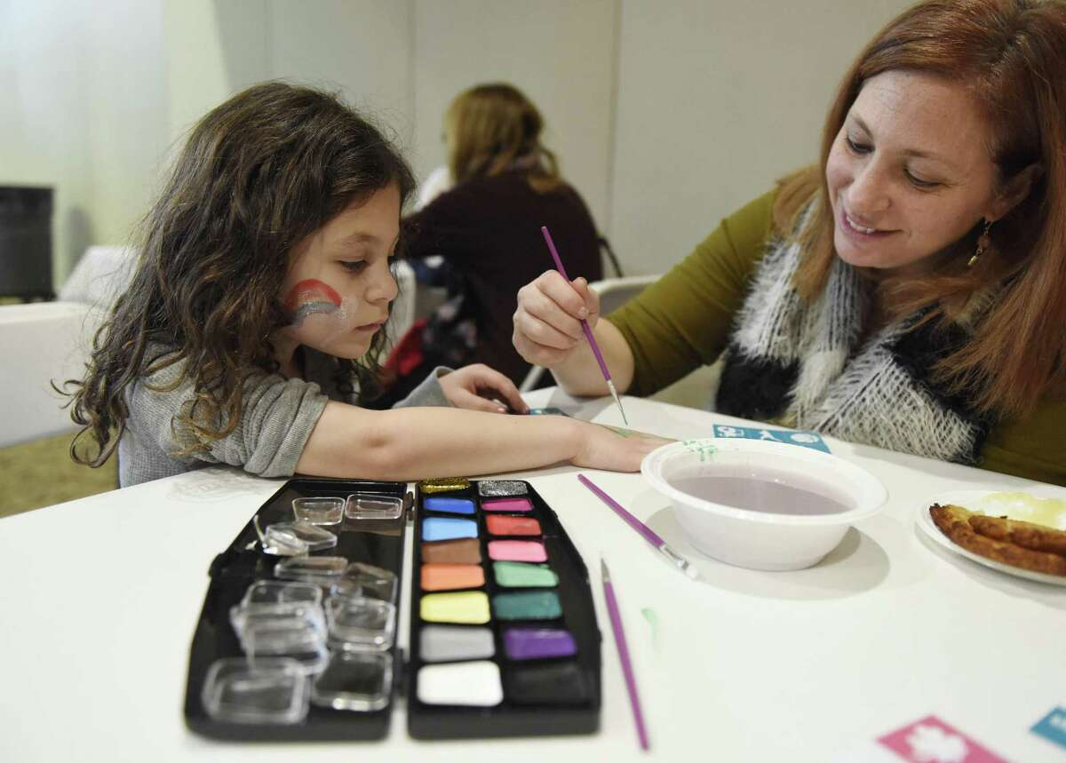 Stamford's Sarah Poland paints a henna tattoo on her daughter, Eve Poland, 5, at the Chanukah Celebration at Temple Sholom in Greenwich, Conn. Sunday, Dec. 10, 2017. The party featured traditional latkes and donuts, an inflatable obstacle course for kids, edible dreidels and menorahs, face painting and other games for kids.