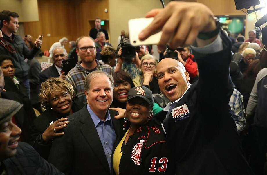 Doug Jones (center), Democrat running for Senate from Alabama, poses Saturday in Montgomery with Sen. Cory Booker, D-N.J. Photo: Joe Raedle