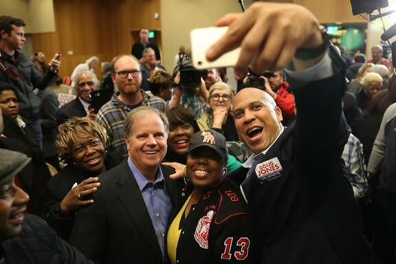 *** BESTPIX *** MONTGOMERY, AL - DECEMBER 09:  Democratic Senatorial candidate Doug Jones takes a group picture with Sen. Cory Booker (D-NJ) (R) and Rep.Terri Sewell (D-AL) (3rd from Right) and supporters during a campaign event held at Alabama State University at the John Garrick Hardy University Student Center on December 9, 2017 in Montgomery, Alabama. Mr. Jones is facing off against Republican Roy Moore in next week's special election for the U.S. Senate.  (Photo by Joe Raedle/Getty Images)