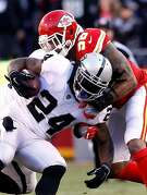 KANSAS CITY, MO - DECEMBER 10:  Running back Marshawn Lynch #24 of the Oakland Raiders carries the ball as inside linebacker Derrick Johnson #56 of the Kansas City Chiefs makes the stop during the game at Arrowhead Stadium on December 10, 2017 in Kansas City, Missouri.  (Photo by Jamie Squire/Getty Images)