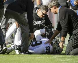 Oakland Raiders trainers look over Oakland Raiders wide receiver Amari Cooper (89) during the first half of an NFL football game against the Kansas City Chiefs in Kansas City, Mo., Sunday, Dec. 10, 2017. (AP Photo/Charlie Riedel)