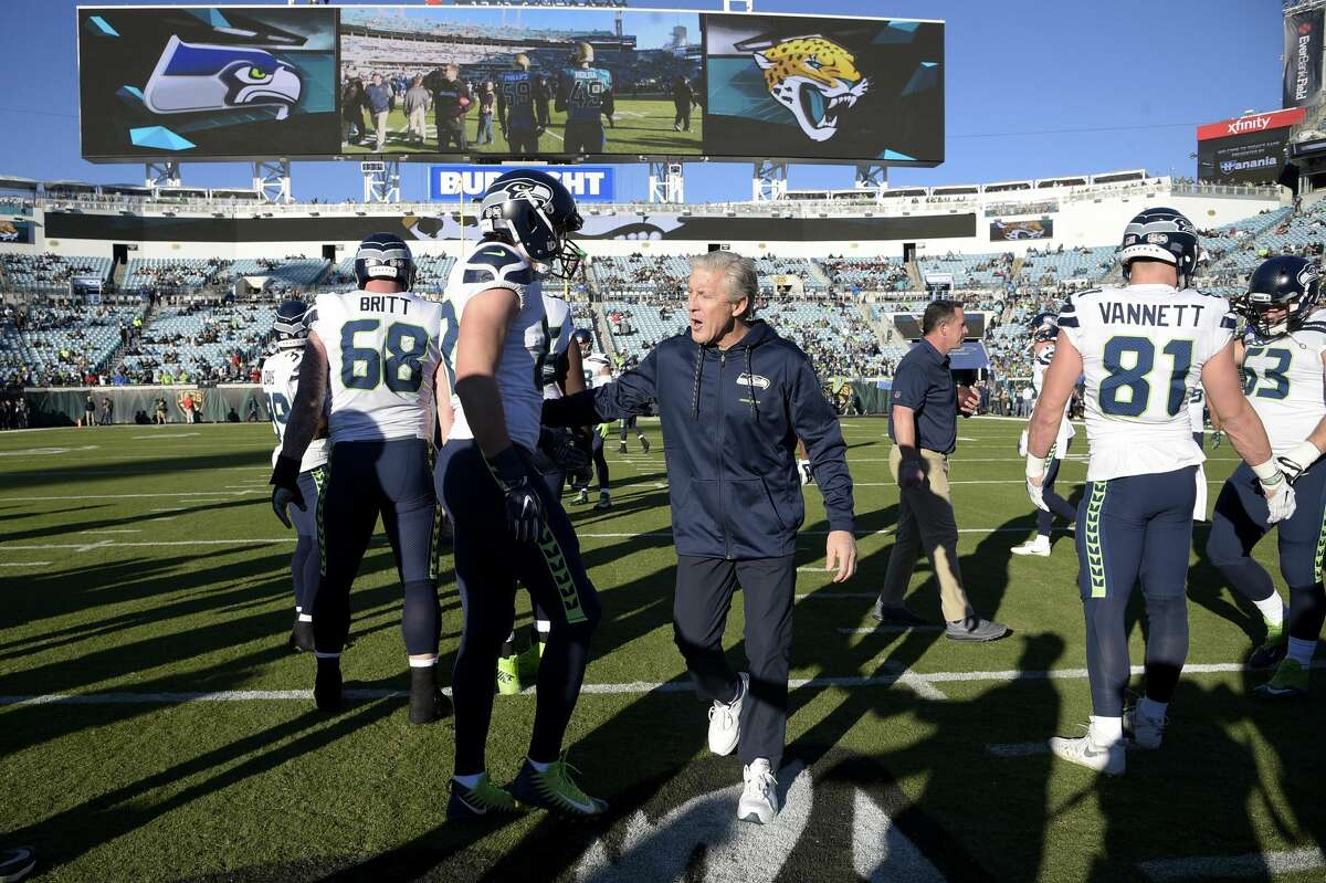 Seattle Seahawks head coach Pete Carroll, center, talks with tight end Luke Willson (82), left, before an NFL football game against the Jacksonville Jaguars Sunday, Dec. 10, 2017, in Jacksonville, Fla.