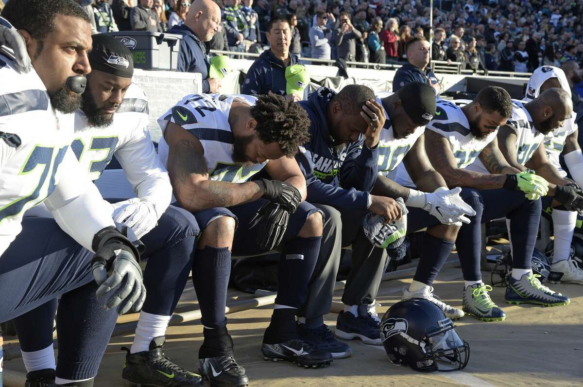 Seattle Seahawks players kneel during the national anthem before the first half of an NFL football game against the Jacksonville Jaguars, Sunday, Dec. 10, 2017, in Jacksonville, Fla. (AP Photo/Phelan M. Ebenhack)