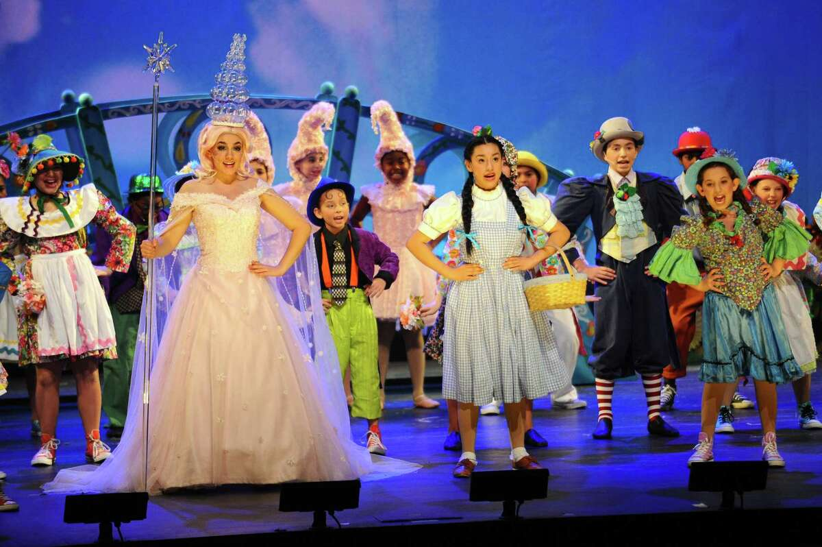 """Victoria Iparraguirre, as Dorothy Gale (center right), and Ava Spinelli Mastrone, as Glinda the Good Witch, lead the chorus in singing """"Munchkin Musical Sequence"""" during the 11th annual 2017 Stamford all-school musical, The Wizard of Oz, at Westhill High School on Sunday, Dec. 10, 2017."""