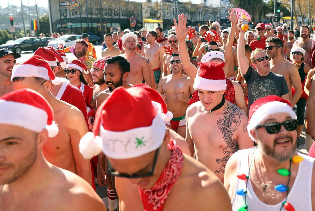 Runners react as they approach the finish line of the Santa Skivvies Run in the Castro District in San Francisco, Calif., on Sunday, December 10, 2017.