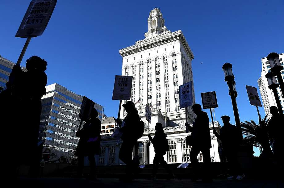 City workers carry signs as they picket outside of Oakland City Hall on Tuesday. Photo: Justin Sullivan, Getty Images