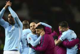 Manchester City's David Silva, center left, celebrates with teammate Sergio Aguero at the end of the English Premier League soccer match between Manchester United and Manchester City at Old Trafford Stadium in Manchester, England, Sunday, Dec. 10, 2017. City won 2-1. (AP Photo/Dave Thompson)