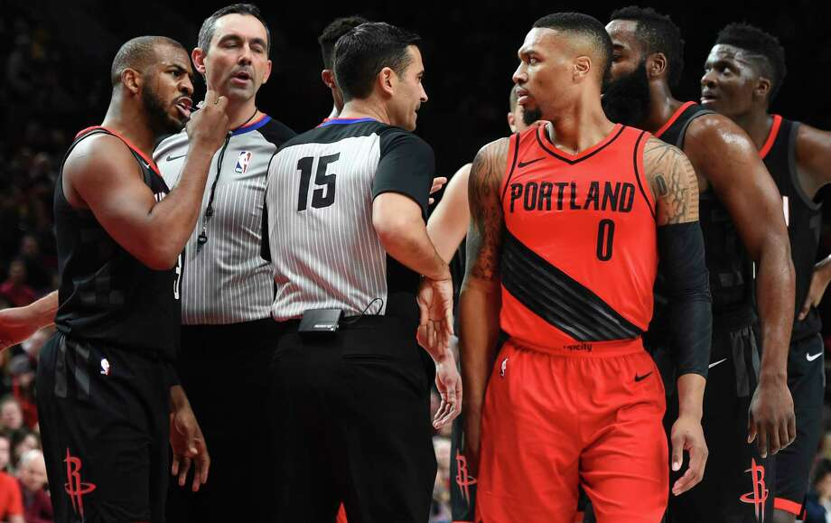 Rockets guard Chris Paul, left, has words with Trail Blazers guard Damian Lillard (0) after knocking Lillard down and being called for a foul during Saturday night's first half at Portland. Photo: Steve Dykes, FRE / FR155163 AP