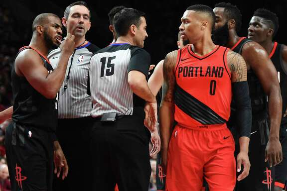 Rockets guard Chris Paul, left, has words with Trail Blazers guard Damian Lillard (0) after knocking Lillard down and being called for a foul during Saturday night's first half at Portland.