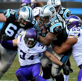 Carolina Panthers running back Jonathan Stewart, center/right, keeps pushing forward on a run as Minnesota Vikings safety Andrew Sendejo, left, and linebacker Anthony Barr, right, try to make the stop during fourth quarter action on Sunday, Dec. 10, 2017 at Bank of America Stadium in Charlotte, N.C. The Panthers defeated the Vikings 31-24. (Jeff Siner/Charlotte Observer/TNS)