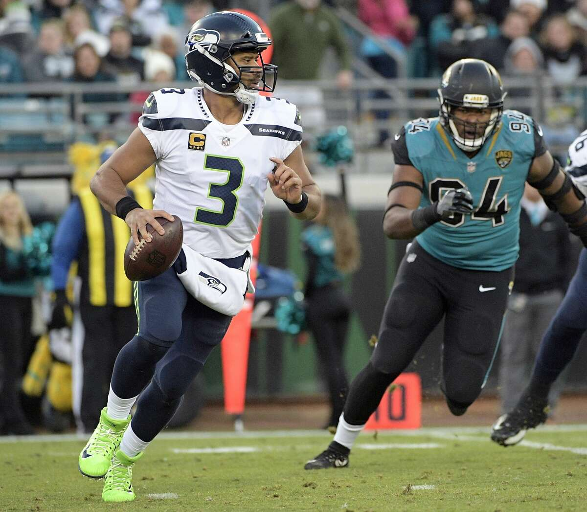 Seattle Seahawks quarterback Russell Wilson (3) scrambles as he is pressured by Jacksonville Jaguars defensive end Dawuane Smoot (94) during the first half of an NFL football game, Sunday, Dec. 10, 2017, in Jacksonville, Fla. (AP Photo/Phelan M. Ebenhack)