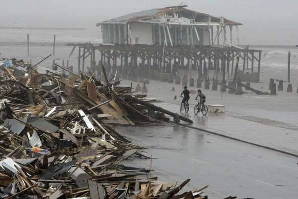 Nine entities are still awaiting payment of nearly $60 million for claims filed over damages from Hurricane Ike in 2008 from the Texas Windstorm Insurance Association, a quasi-governmental group that serves as an insurer of last resort for an area of coastal Texas that includes 14 counties and a slice of Harris County. In this 2008 photo, cyclists ride past debris piled up on the seawall road after Hurricane Ike hit the Texas coast in Galveston.