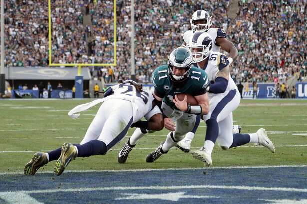 LOS ANGELES, CA - DECEMBER 10:  Carson Wentz #11 of the Philadelphia Eagles is hit by Mark Barron #26 of the Los Angeles Rams during the third quarter of the game.  Wentz was later escorted off the field due to a knee injury at the Los Angeles Memorial Coliseum on December 10, 2017 in Los Angeles, California.  (Photo by Jeff Gross/Getty Images)
