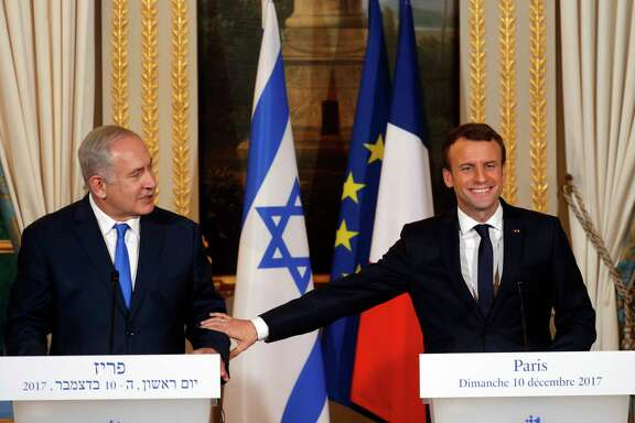 "French President Emmanuel Macron, right, and Israeli Prime Minister Benjamin Netanyahu attend a press conference after a meeting at the Elysee Palace in Paris, Sunday, Dec.10, 2017. French President Emmanuel Macron ""firmly and clearly"" condemns all kinds of attacks against Israel in recent hours and days and reaffirmed his ""disapproval"" of U.S. President Donald Trump's move to recognize Jerusalem as the capital of Israel. (Philippe Wojazer/Pool via AP)"