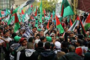 Protesters chant slogans as they hold Palestinian flags during a demonstration in front of the U.S. embassy in Aukar, east of Beirut, Lebanon, Sunday, Dec. 10, 2017. A few hundred demonstrators, including Palestinians, pelted security outside the embassy with stones and burned an effigy of U.S. President Donald Trump in a protest to reject Washington's recognition of Jerusalem as capital of Israel. (AP Photo/Bilal Hussein)
