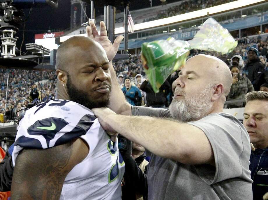 A Seattle Seahawks staff member tries to remove Seahawks defensive tackle Quinton Jefferson, left, from the field as an object thrown from the stands hits them during the closing moments of an NFL football game against the Jacksonville Jaguars, Sunday, Dec. 10, 2017, in Jacksonville, Fla. Jacksonville won 30-24. (AP Photo/Stephen B. Morton) Photo: Stephen B. Morton/AP